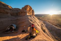 Tourist man prepearing campground with a ten in mountain desert at sunset time. Travel lifestyle photo.  Stock Photo