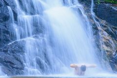 Tourist man relaxing under flowing waterfall nature. Nature Ther. Apy. Summer season. Khao Lak, Thailand. Slow shutter speed Royalty Free Stock Photos