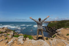 Tourist man on the rocky shore of sea. Royalty Free Stock Photography