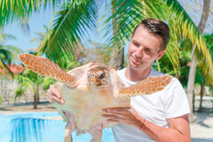 Tourist man with sea turtle in the hands in exotic reserve Stock Images