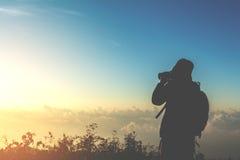 Tourist man shoot photo on peak of mountain Royalty Free Stock Images