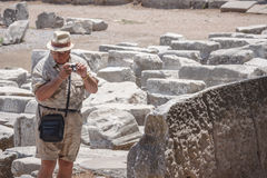 Tourist man is shooting photos in Ephesus. A tourist man is shooting photos in Ephesus: antique greek, later roman, city in the actual Turkey; near Izmir. The Stock Image