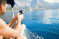 Tourist man siitng in boat and photographing sea. Tourist man siitng in boat and photographing beautiful sea Stock Photography