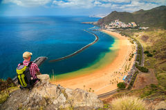 Tourist man sitting on the edge of a cliff Royalty Free Stock Photo