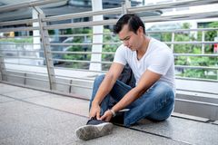 Tourist man sitting on floor take off the shoes massaging feet walking a lot of foot pain after a long walk. Ache ankle care casual cramp damage discomfort royalty free stock photography