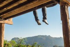 Tourist man sitting legs hanging on terrace Royalty Free Stock Photos