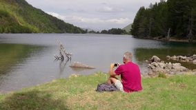 Tourist man sitting next to the mountain lake and take a picture with mobile phone.  stock footage