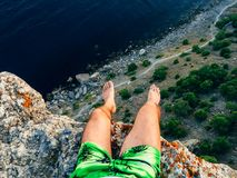 Tourist man sitting on top of a mountain over the sea royalty free stock photo