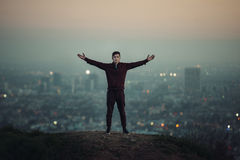 Tourist man standing on the hill with hands raised up next to big city light Stock Photo