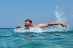 Tourist man in swimming sports glasses is floating in the Aegean Sea on the coast of Sithonia Peninsula Royalty Free Stock Photos