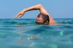 Tourist man in swimming sports glasses is floating in the Aegean Sea on the coast of Sithonia Peninsula Stock Photography