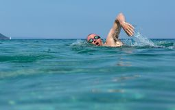 Tourist man in swimming sports glasses is floating in the Aegean Sea on the coast of Sithonia Peninsula. Tourist man in swimming sports glasses is floating in Stock Images