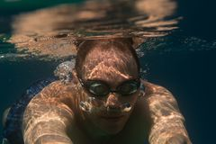 Tourist man in swimming sports glasses swimming underwater in the Aegean Sea on the coast of Sithonia Peninsula Stock Photography
