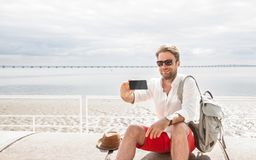 Tourist man takes a photo of himself selfie with phone smartphone stock images