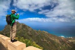 Tourist man taking the landscape photograph Stock Photos