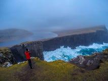 Tourist man taking photo on high cliffs, Faroe Islands, Denmark