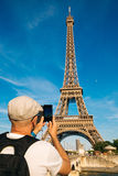 Tourist man taking pictures of the Eiffel Tower with a smart pho Stock Image