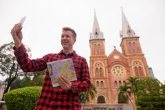 Tourist man taking selfie in front of Notre Dame Cathedral in Ho Chi Minh City. Portrait of young handsome tourist man exploring Ho Chi Minh city in Vietnam royalty free stock photos