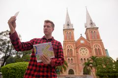 Tourist man taking selfie in front of Notre Dame Cathedral in Ho Chi Minh City. Portrait of young handsome tourist man exploring Ho Chi Minh city in Vietnam royalty free stock images