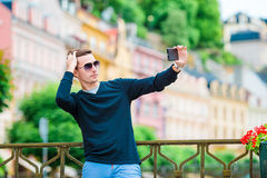 Tourist man taking travel photos with smartphone on summer holidays. Young attractive tourist taking selfie photo with Royalty Free Stock Photography