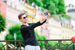 Tourist man taking travel photos with smartphone on summer holidays. Young attractive tourist taking selfie photo with Royalty Free Stock Image