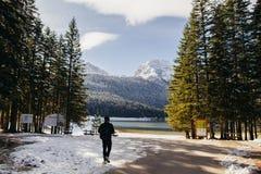 Tourist man travel to snowy mountains background Stock Photography