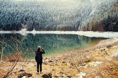 Tourist man travel to snowy mountains background Royalty Free Stock Photos