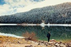 Tourist man travel to snowy mountains background Royalty Free Stock Photo