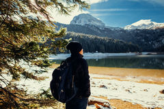 Tourist man travel to snowy mountains background Royalty Free Stock Images