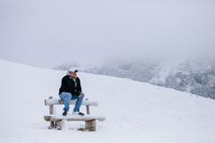Tourist man travel to snowy mountains background Royalty Free Stock Image