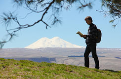 Tourist with a map and a backpack on a background of mount Elbru Stock Photos
