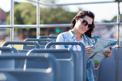 Tourist map bus. Tourist looking at map while on an open top bus touring the city Stock Image