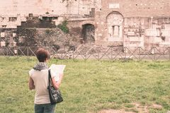 Tourist with map getting around ancient ruins in Rome old town, Appia Antica way, heritage of early italian history, travel destin Stock Photo