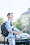 Young tourist with map. A man looking where he is using a map Royalty Free Stock Image
