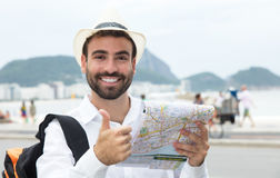 Tourist with map at Rio de Janeiro showing thumb up Royalty Free Stock Image