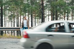 Tourist with map standing on road. With riding car stock photo
