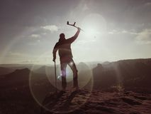 Tourist with medicine crutch above head achieve mountain peak. Hurt backpacker with broken leg Royalty Free Stock Photography