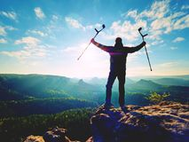 Tourist with medicine crutch above head achieve mountain peak. Hurt backpacker with broken leg Royalty Free Stock Photos