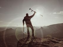 Tourist with medicine crutch above head achieve mountain peak. Hurt backpacker with broken leg Royalty Free Stock Image