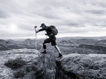 Tourist with medicine crutch above head achieved mountain peak. Hiker with broken leg. In immobilizer. Deep misty valley bellow silhouette of happy man with Stock Photo
