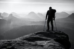 Tourist mit dem Bein in der Wegfahrsperre Wandererschattenbild mit Medizinkrücke auf Berg Lizenzfreie Stockbilder