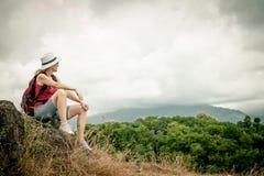Tourist mit dem Rucksack, der auf Felsen sich entspannt und das Bewundern genießt Lizenzfreie Stockfotografie