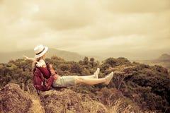 Tourist mit dem Rucksack, der auf Felsen sich entspannt und das Bewundern genießt Lizenzfreies Stockfoto