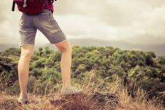 Tourist mit dem Rucksack, der auf Felsen sich entspannt und das Bewundern genießt Stockfotografie