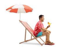 Tourist mit einem Cocktail, das in einem Klappstuhl mit einem Regenschirm sitzt Lizenzfreie Stockbilder