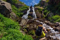 Tourist mit einem Rucksack, der durch einen Wasserfall in den Bergen sitzt lizenzfreie stockfotos