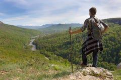 Tourist mit einem Stock und einem Rucksack auf einem Hintergrund von Bergen Stockbilder
