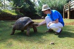 Tourist mit riesiger Schildkröte Stockbilder