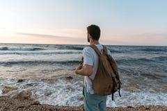 Tourist mit Rucksack den Sonnenuntergang über dem Meer aufpassend Stockfotografie