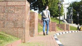 Tourist mit Rucksack geht entlang Bürgersteig stock video